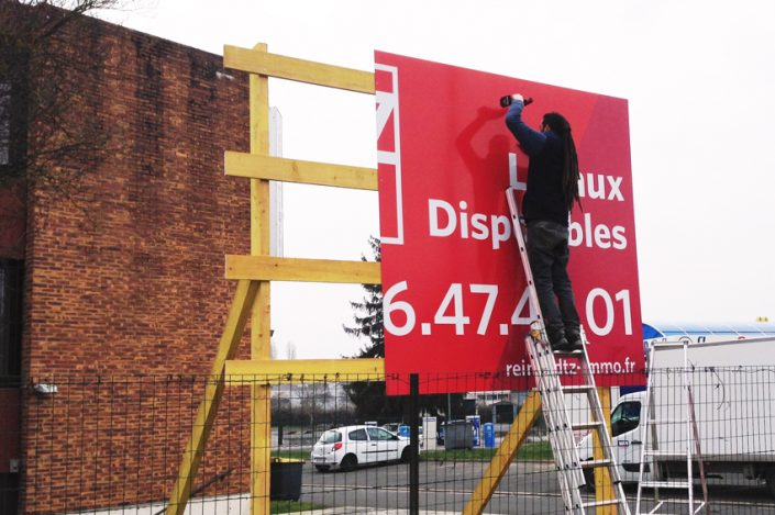 Pose panneau de chantier DTZ Cushman&Wakefield communication